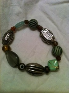 "Beaded bracelet, some glass in  shades of green (turquoise),   amber, and silver.   7"" length"