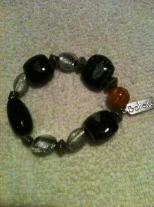 "Glass beaded bracelet in hues of  black, silver, and clear beads with  a ""believe"" charm. 8"" in length"